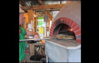 Heather Secrist of Suncrest Gardens Pizza Farm pulls a pizza from her oven. (Photo by Breann Schossow)