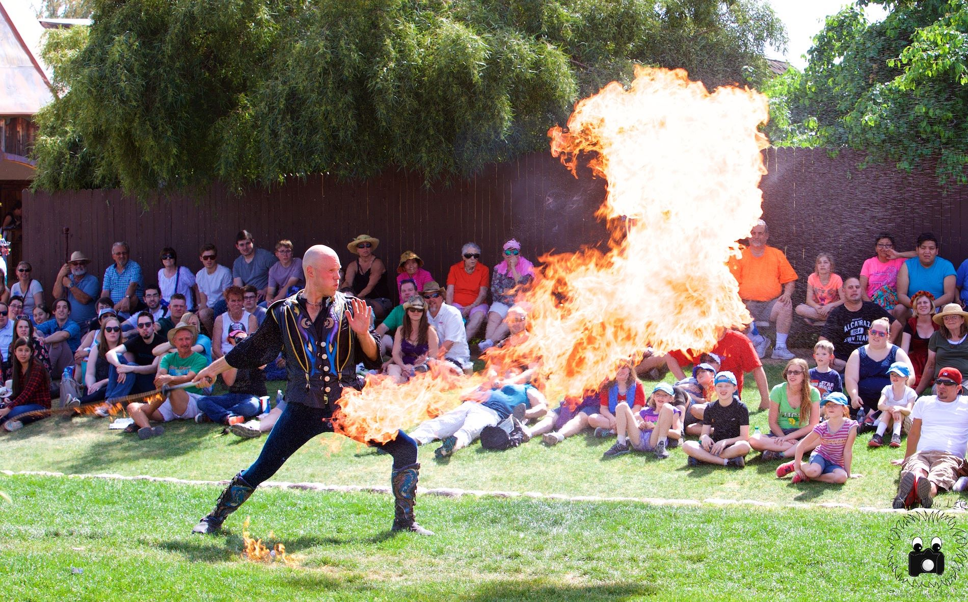 "Adam ""Crack"" Winrich cracks a fire whip at a Renaissance Fair in Wisconsin before a crowd of people."