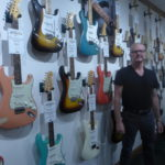 Dave Rogers stands in front of a wall of Fender guitars. These make up some of his private collection at Dave's Guitar Shop in La Crosse, Wisconsin.