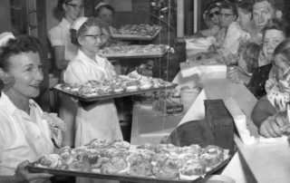 Four bakers are holding up large trays laden with fresh cream puffs at a State Fair midway concession stand, while an eager crowd stands waiting in anticipation on the other side of the counter.