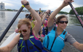 Debbie Koenig (left) and Terri Pedace paddle with the Mississippi Sisters, a dragon boat racing team. Coach Lori Freit-Hammes stands at the back of the boat.