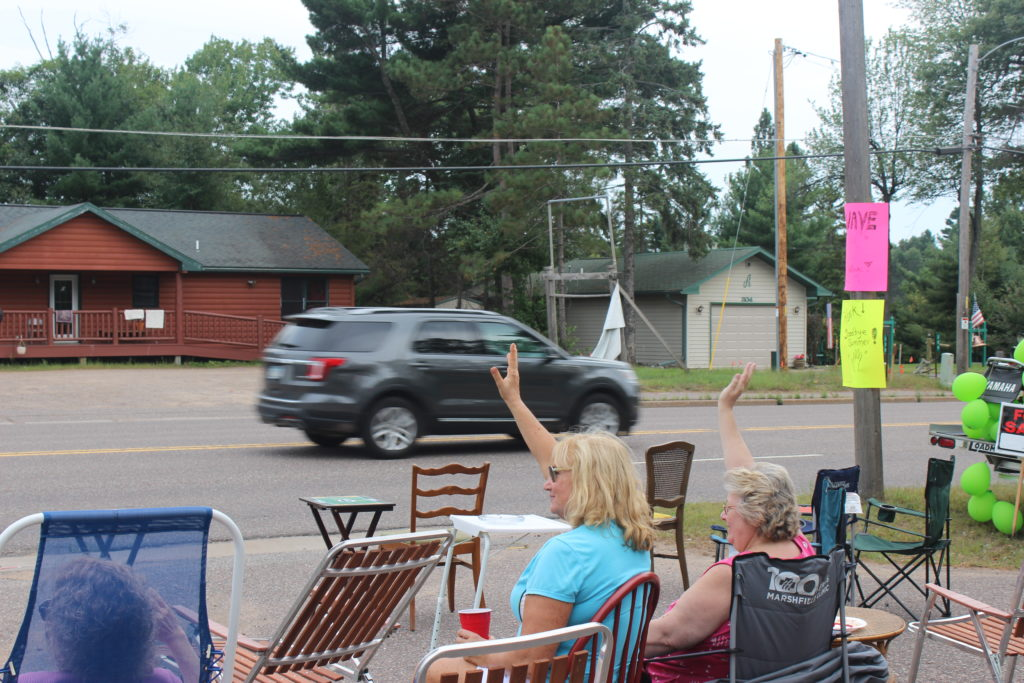 People wave to cars headed south on Highway 51 in Arbor Vitae, Wisconsin.
