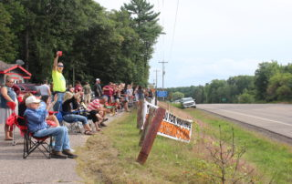 People wave good-bye to tourists at Whitman's Bar & Grill in Hazelhurst, WI.
