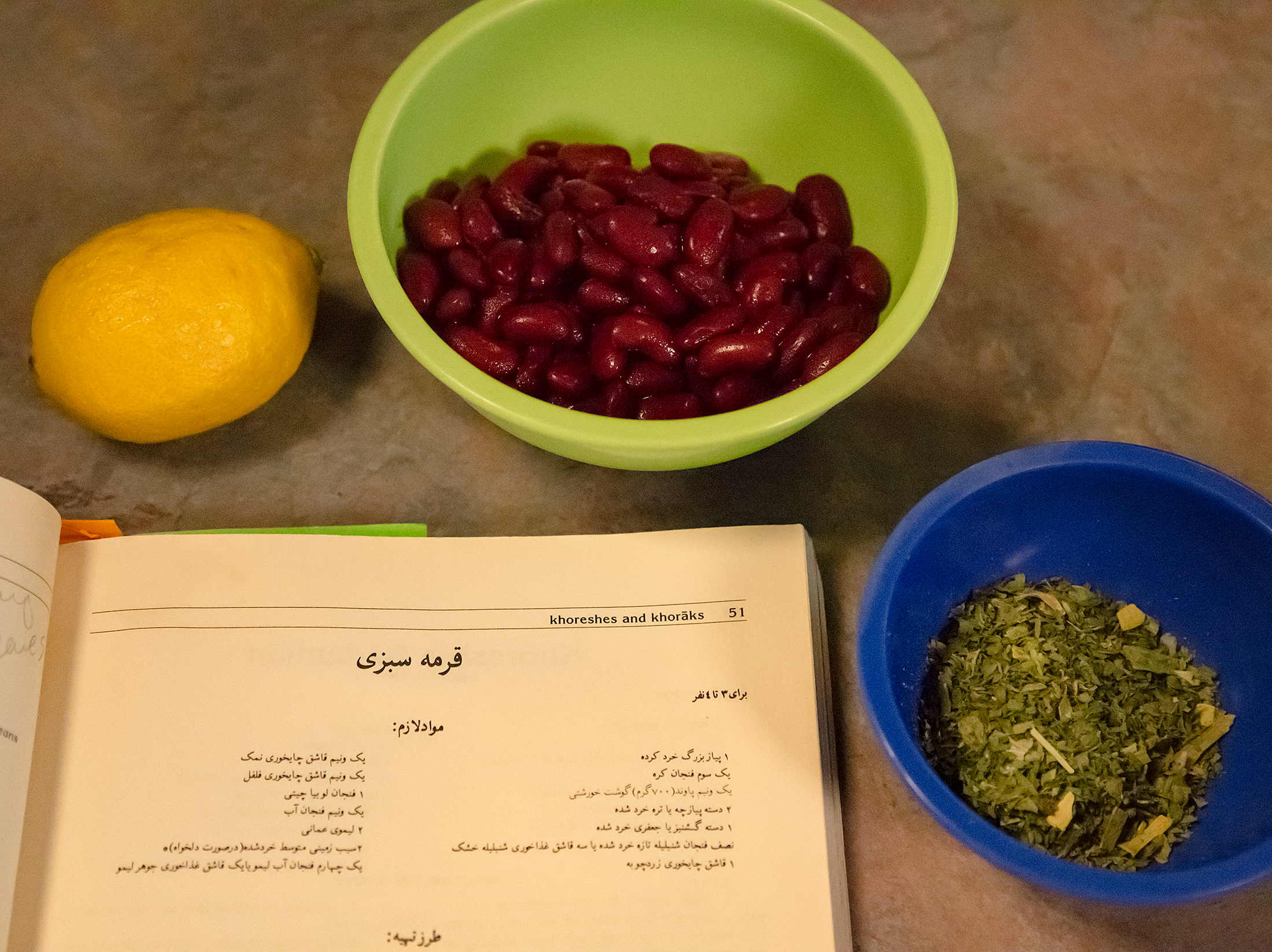 A lemon, kidney beans, minced parsley and a Persian cookbook