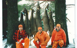 Brothers Jim, Gary, and Ron Weber: hunting partners among the trees with their deer.