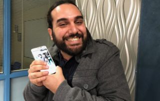 Esteban Touma with his cell phone. (Maureen McCollum/WPR)