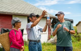Chia and Cheu Vang talk with Roger Hake at Vang C&C Vegetable Farm in Jefferson County. (Photo by Max Cozzi for The Lands We Share)