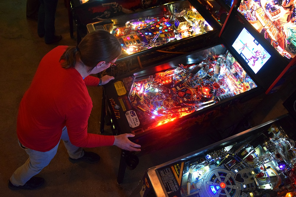 Hilton Jones, co-founder of Madison Pinball, plays the Deadpool pinball machine at I/O Arcade Bar in Madison, Wis. (Jenny Peek/WPR)