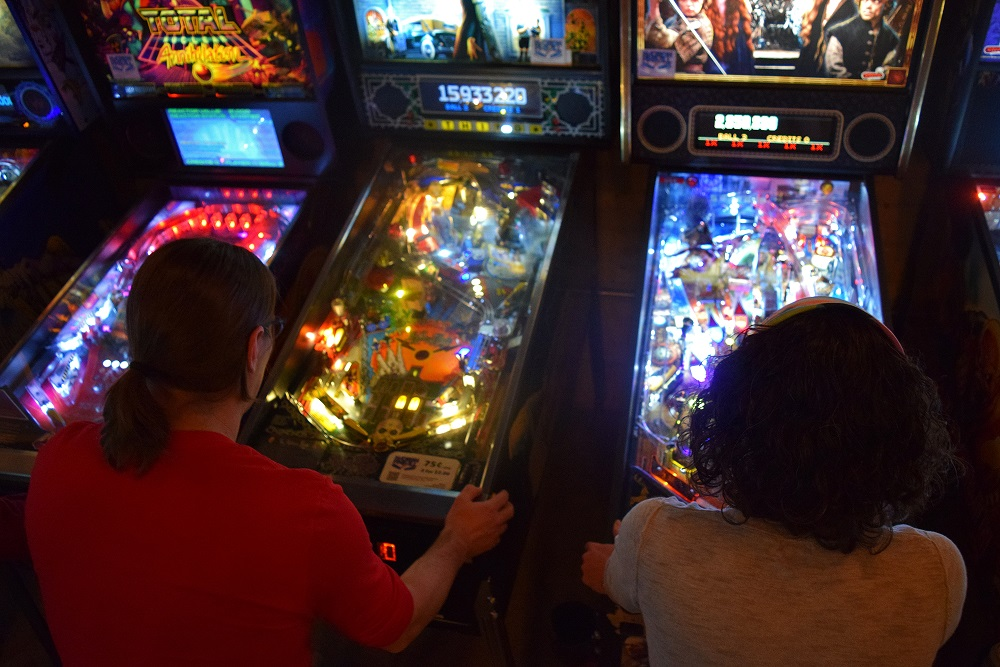 Hilton and Heidi Jones play pinball at Madison's I/O Arcade Bar. (Jenny Peek/WPR)
