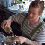 Merchant bar manager Lucas Endres mixes a Breakfast with Petey Pablo cocktail. (Jenny Peek/WPR)