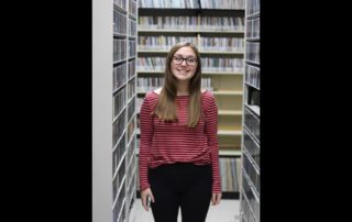 MG21 student Abbie Pochel in WPR's music library during a field trip. (Jenny Peek/WPR)