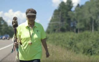 "Healing Circle Run participant Agnes Fleming walks with her husband's staff. (Still from ""Every Step: A Healing Circle"")"
