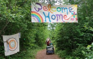 "A sign reads ""Welcome Home"" at the beginning of the trail leading to the main meadow area of the Rainbow Family gathering on July 4, 2019. (Danielle Kaeding/WPR)"