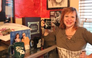 GinGee Girls owner and artist Sunshine Levy shows off a mug she sandblasted alongside memorabilia from comic cons. (Photo by Victoria Davis)