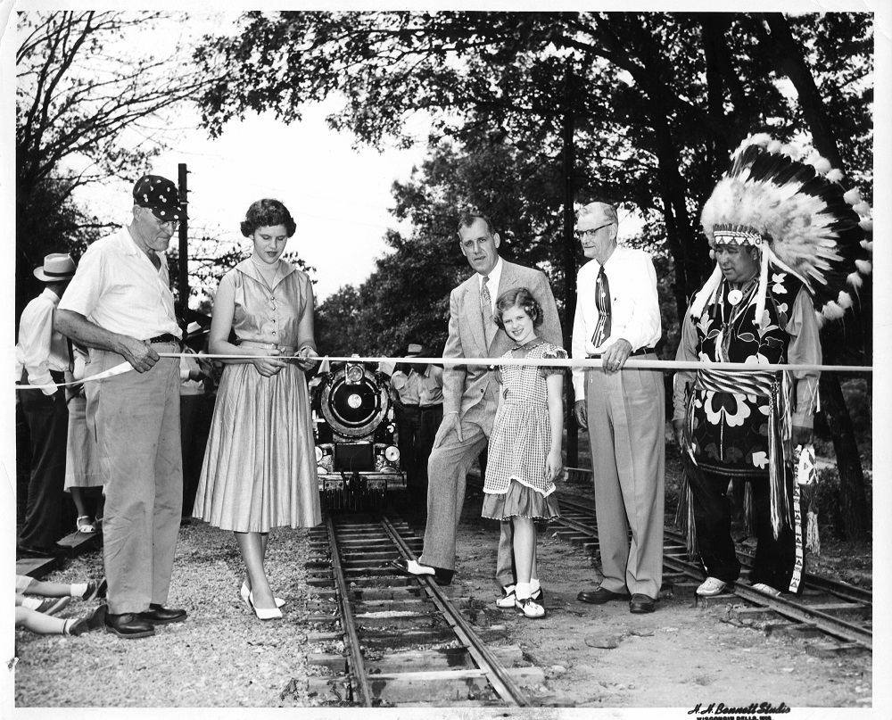 The Riverside & Great Northern Railway held a grand opening in Wisconsin Dells on August 9, 1953. From left to right: Elmer Sandley, Judith Johnston, Milwaukee Road general passenger agent R.F. Johnston, Carol Johnston, Grover Belton, and Chief Yellow Thunder of the Ho-Chunk Nation. (Photo by H.H. Bennett Studio)