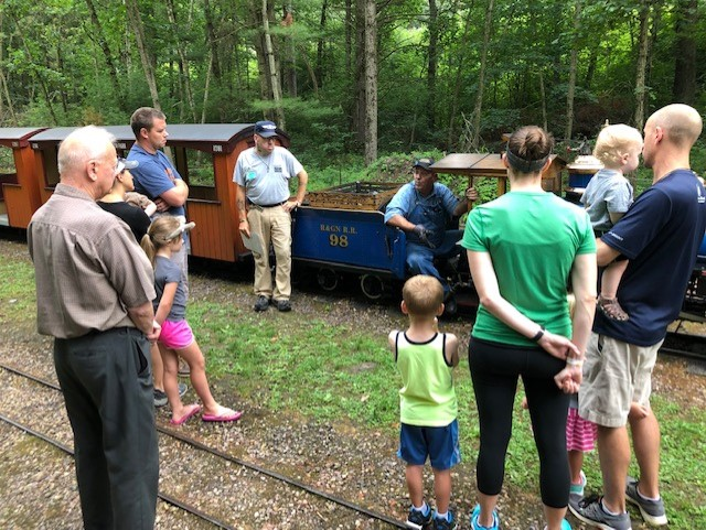Riverside & Great Northern Railway Preservation Society President Steven Bradley (seated) talks with families about to ride the train. (Courtney Everett/WPR)