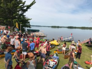 Participants with their kayaks and canoes ready themselves at the edge of the Wisconsin River flowage before the launch of PaddleQuest 2019. (Rob Mentzer/WPR)