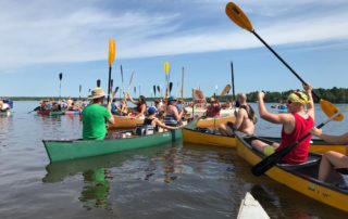 Paddles up and cheers go out as the 2019 PaddleQuest sets off. (Rob Mentzer/WPR)