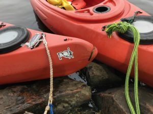 A PaddleQuest logo is displayed on the front of a participant's kayak. (Rob Mentzer/WPR)