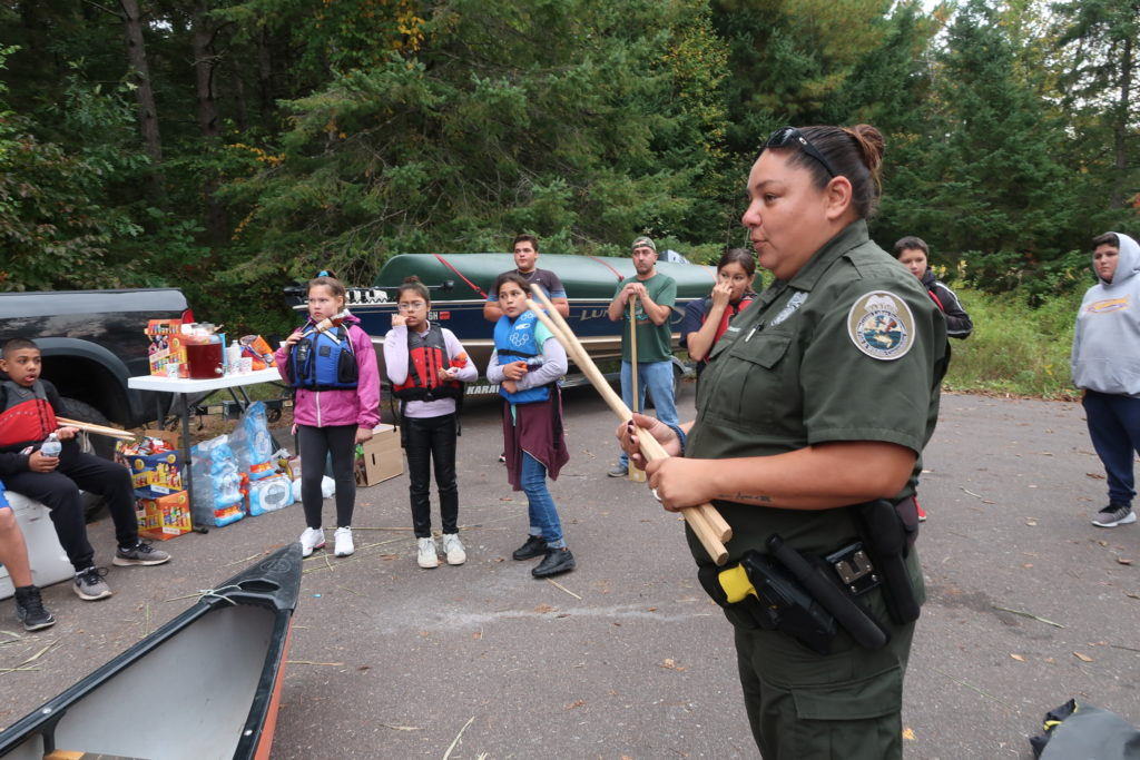 Christine Dzwonkowski, a warden with the Great Lakes Indian Fish and Wildlife Commission, gives Bad River youth a tutorial on how to harvest wild rice at Pacwawong Lake. (Danielle Kaeding/WPR)