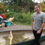 Seventeen year-old Kreighton Wolf is the chairwoman of the Bad River Youth Council. She stands next to a canoe filled with wild rice after harvesting on Pacwawong Lake. (Danielle Kaeding/WPR)