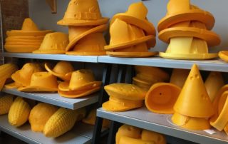 Cheesehead fedoras, cowboy and party hats, and firefighter helmets on display at Foamation's factory store in Milwaukee. (Maureen McCollum/WPR)
