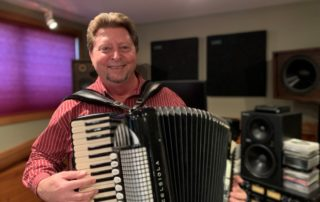 Steve Meisner plays the accordion in his home studio. (Brad Kolberg/WPR)
