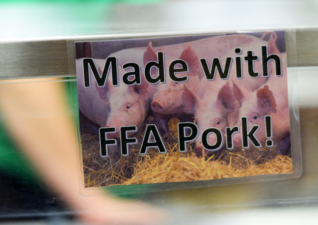 A sign notifies people who pass through the lunch line at Holmen High School that the marinara sauce was made with pork from pigs raised by FFA students. (Liz Dohms/WPR)