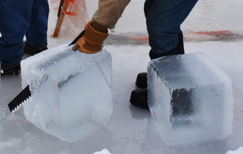 "A volunteer saws a layer of soft ice off a block of ice at the Historic Point Basse ice harvesting demonstration, Jan. 26, 2020 at Nepco Lake. ""The crystal clear ice is the stuff that really keeps well,"" said volunteer Mike Hittner. (Rob Mentzer/WPR)"