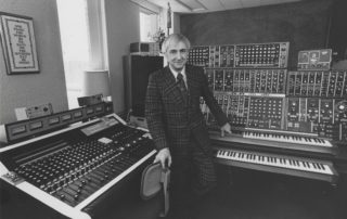 "Don Voegeli stands in front of mixers. Voegeli was the composer of the theme that ""All Things Considered"" has used since the show debuted in 1971."