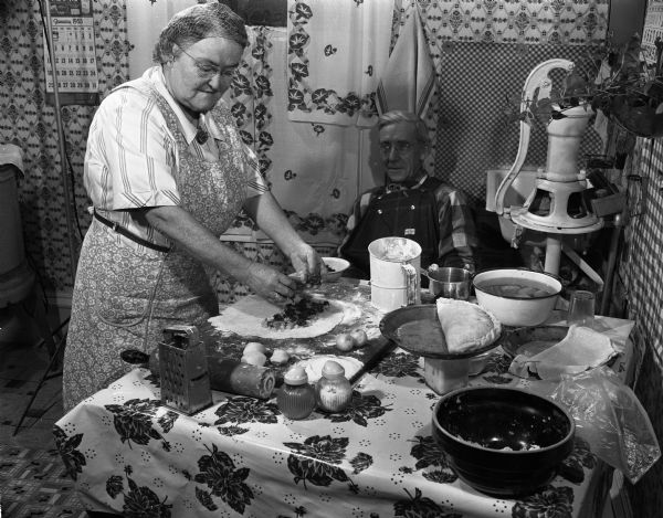 "Woman wearing an apron fills a pasty in her Iowa County, Wisconsin kitchen. A man wearing coveralls is seated at the table watching. (Courtesy of <a href="" https://www.wisconsinhistory.org/Records/Image/IM58386/"" target=""_blank"" rel=""noopener noreferrer"">Wisconsin Historical Society</a>)"