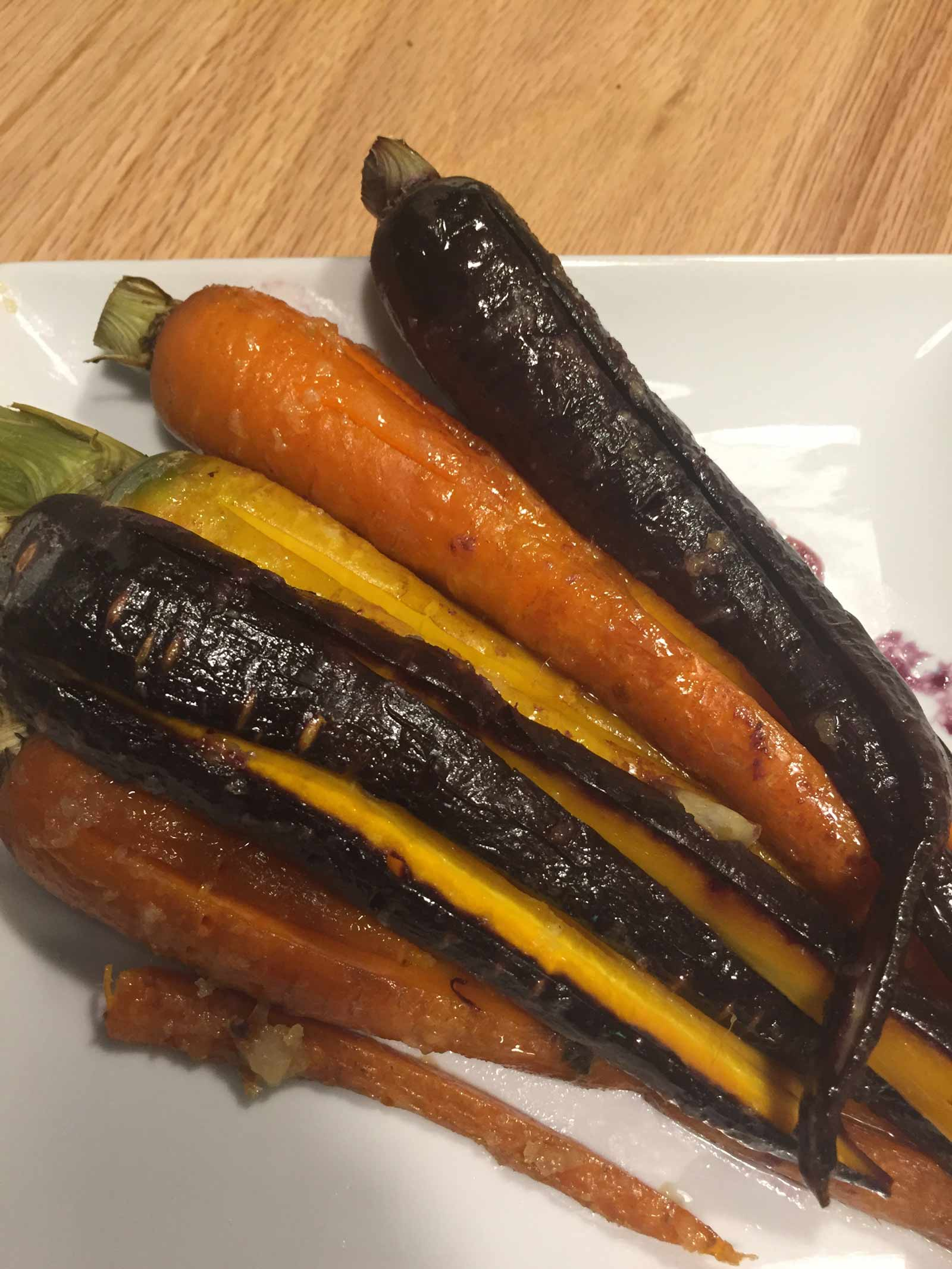 Plate of roasted purple, orange, and yellow carrots.
