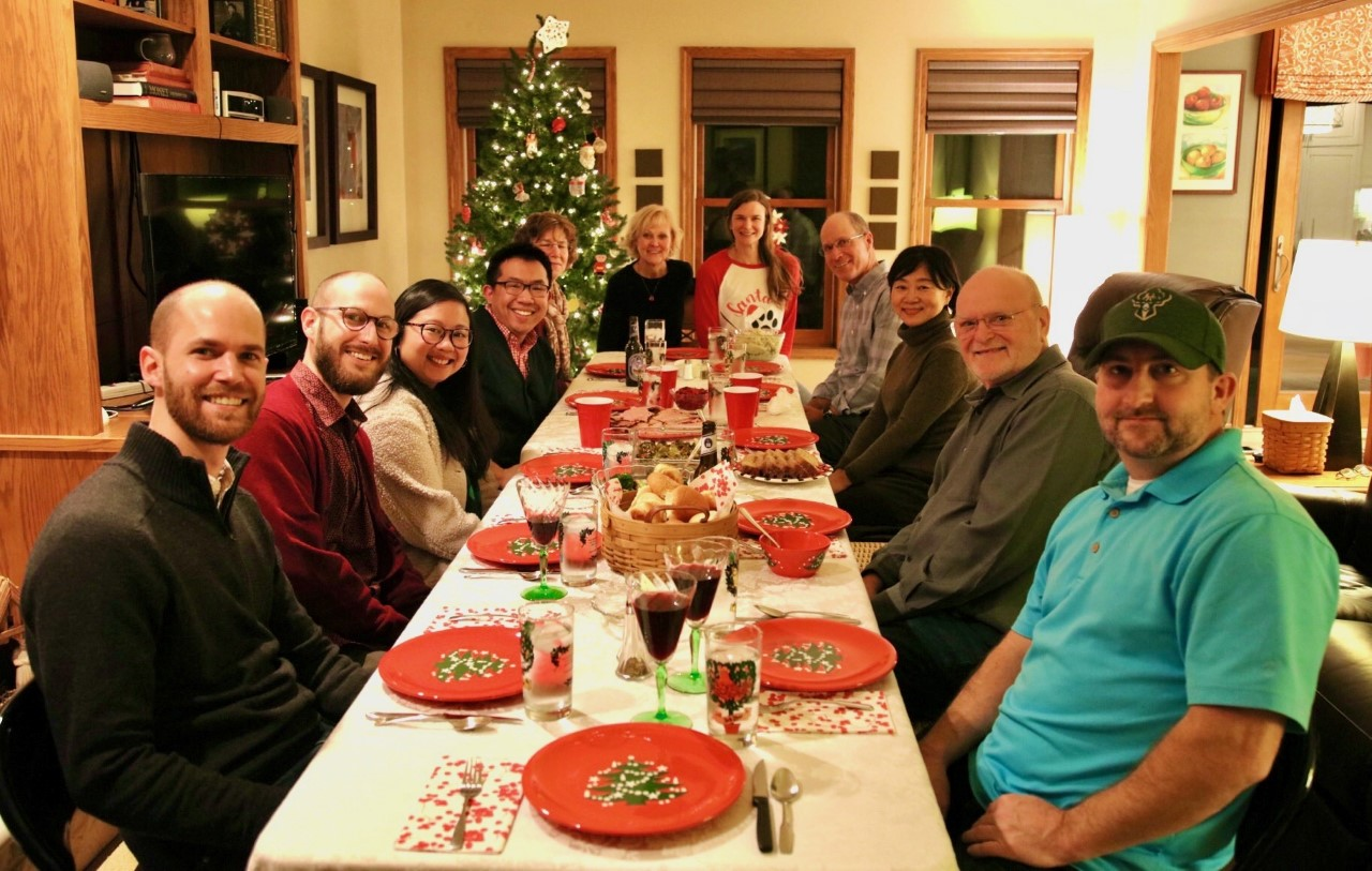 People gathered at Christmas dinner table.