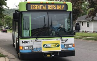 "A sign on a La Crosse bus promotes ""essential trips only"" during the first couple of months of the coronavirus pandemic. Trip restrictions have now loosened for bus systems around Wisconsin. (Kathy Davis/WPR)"