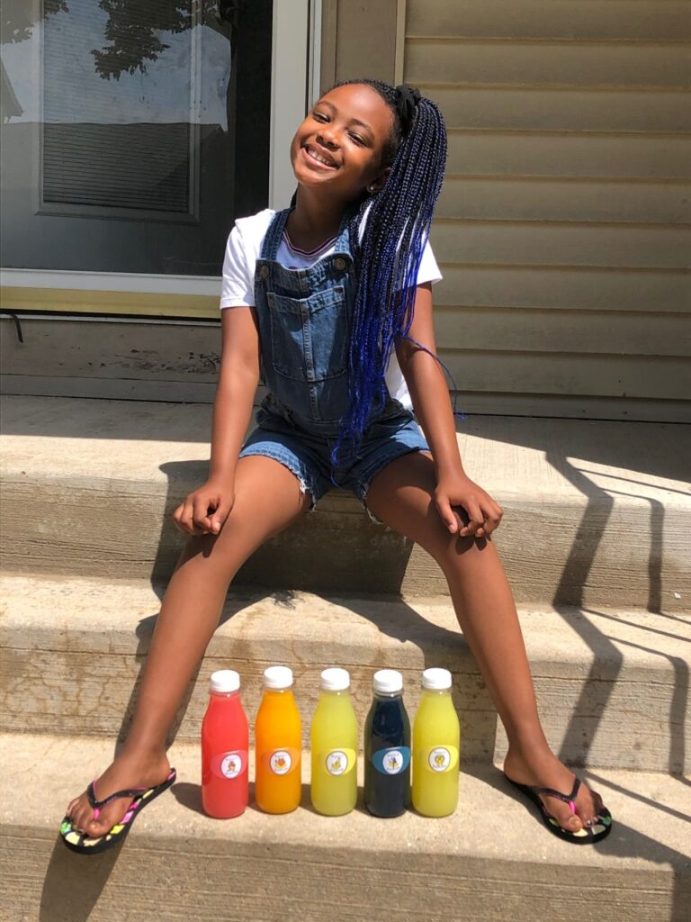 Kyric Burt poses with her lemonade on her front porch. (Maureen McCollum/WPR)