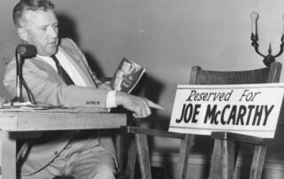 Leonard Schmitt, independent Republican candidate for the U.S. Senate, holds a copy of The McCarthy Record and points to an empty chair with a sign showing the seat reserved for his opponent, Joseph R. McCarthy, to debate the issues with him. (Courtesy of the Wisconsin Historical Society)