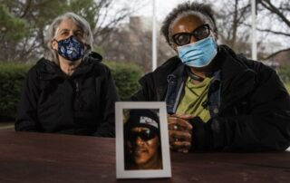 Erin Williams, left, and Dorothy McCollum, right, with a photo of Charles Sheppard, a Navy veteran who helped homeless veterans with his work at the VA. (Angela Major/WPR)