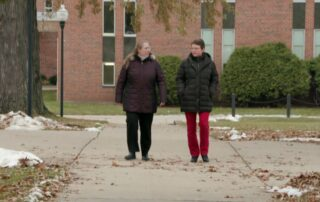 Two women walking together on sidewalk.