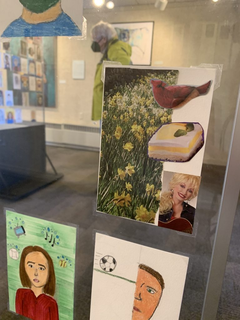 A 79 year-old artist, who signed her name Gloria, made a self-portrait collage featuring daffodils, a cardinal and Dolly Parton. (Megan Hart/WPR)