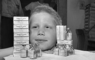 Child posing with polio vaccine bottles and boxes. (Courtesy of Wisconsin Historical Society)